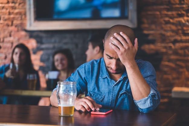 Smutny samotny latynos siedzący w barze lub pubie przy piwie.
