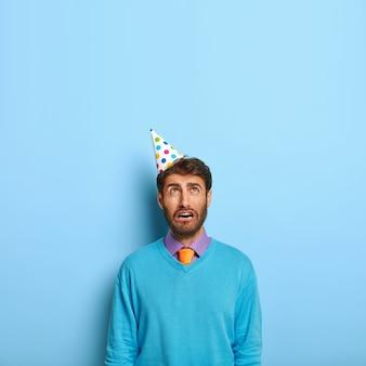 Smutny, samotny urodzinowy mężczyzna nosi stożkowy papierowy kapelusz