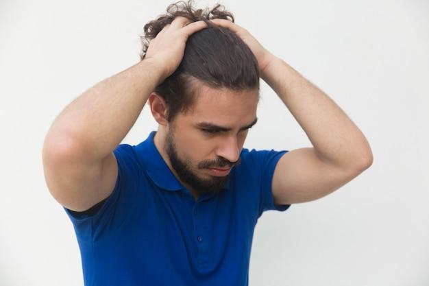 Smutny sfrustrowany facet trzymając głowę obiema rękami