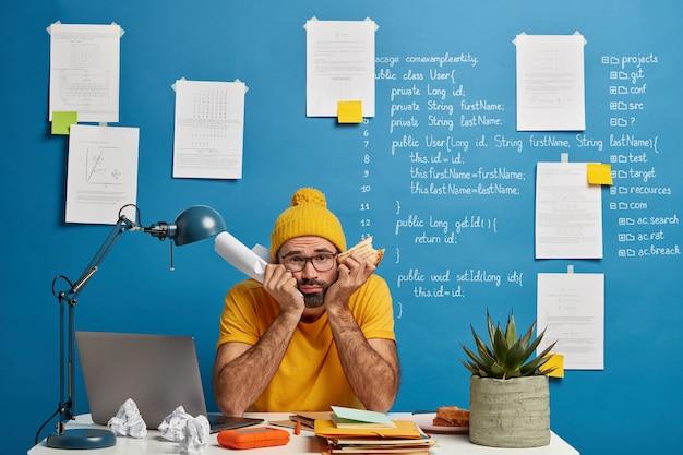 Smutny, sfrustrowany student przygotowuje się do egzaminu z technologii it, trzyma złożony papier i zjada kanapkę z rękami pod brodą i nieszczęśliwie patrzy w kamerę
