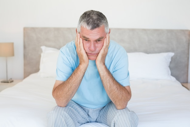 Smutny starszego mężczyzna obsiadanie na łóżku