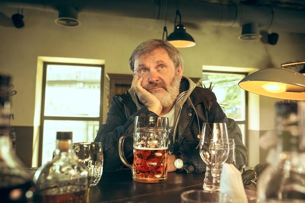Smutny starszy brodaty mężczyzna pije piwo w pubie