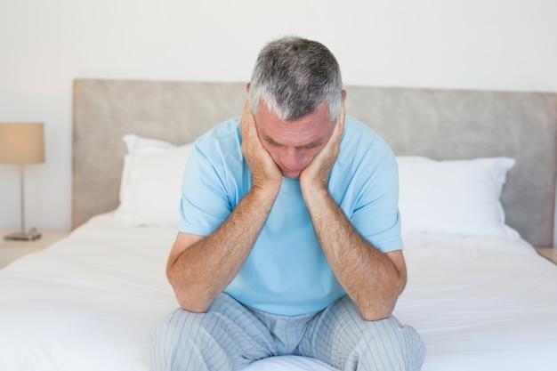 Smutny starszy mężczyzna na łóżku