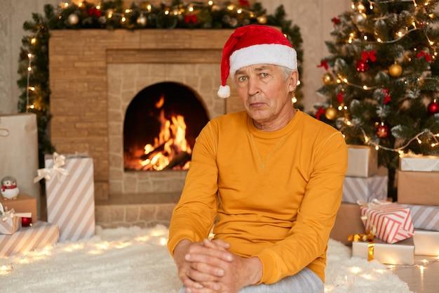 Smutny starszy mężczyzna siedzący w salonie i świętujący samotnie wigilię ma zdenerwowany wyraz twarzy, ubrany w żółty sweter i czapkę świętego mikołaja.