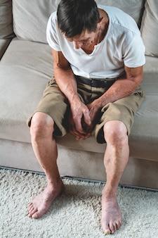 Smutny starszy senior siedzi na kanapie
