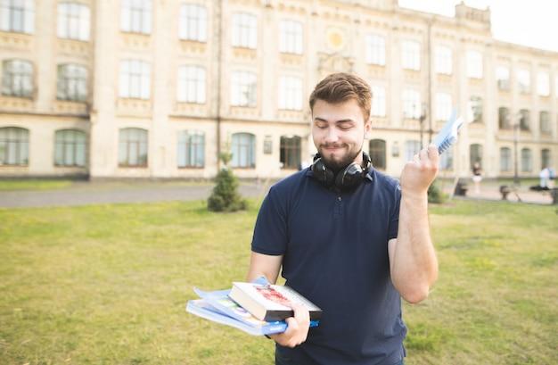 Smutny student z książkami na kampusie