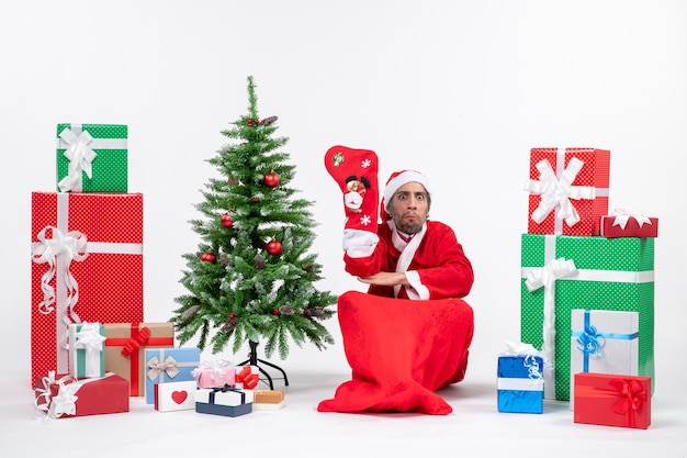 Smutny święty mikołaj siedzi na ziemi i nosi skarpety świąteczne w pobliżu prezentów i udekorowane drzewo noworoczne na białym tle