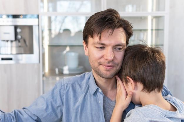 Smutny syn przytulający ojca w domu