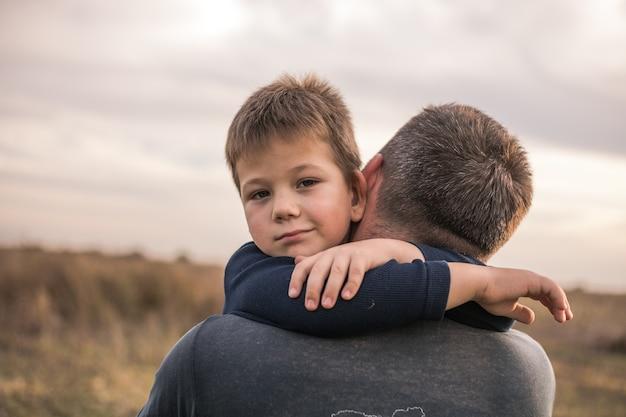 Smutny syn przytulanie tatę na tle łąki