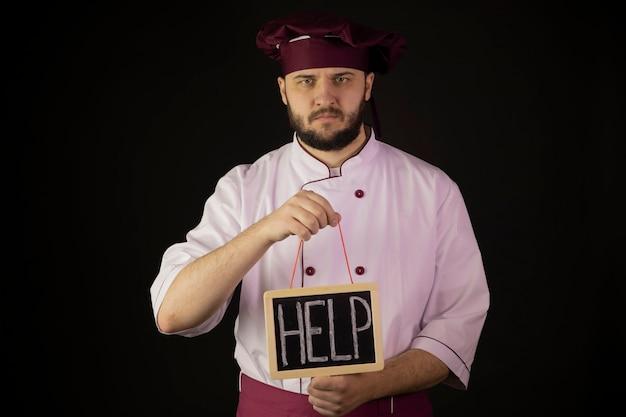 Smutny szef kuchni mężczyzna w mundurze trzyma tablica kredą z napisem pomoc