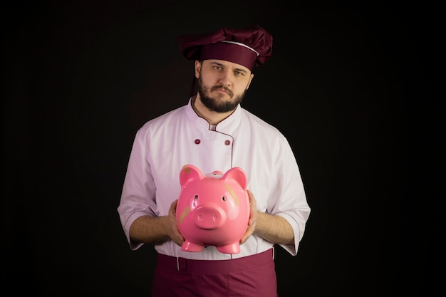 Smutny szef kuchni w mundurze trzyma zepsuty różowa skarbonka z kryzysem pomocy zespołu