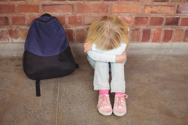 Smutny uczeń siedzi samotnie na ziemi