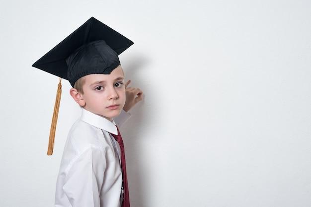 Smutny uczeń w akademickim kapeluszu pisze na pokładzie. łata portret na białej ściany kopii przestrzeni