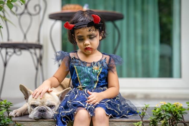 Smutny wyraz twarzy mała dziewczynka w kostiumie na halloween siedząca na zewnątrz z psem