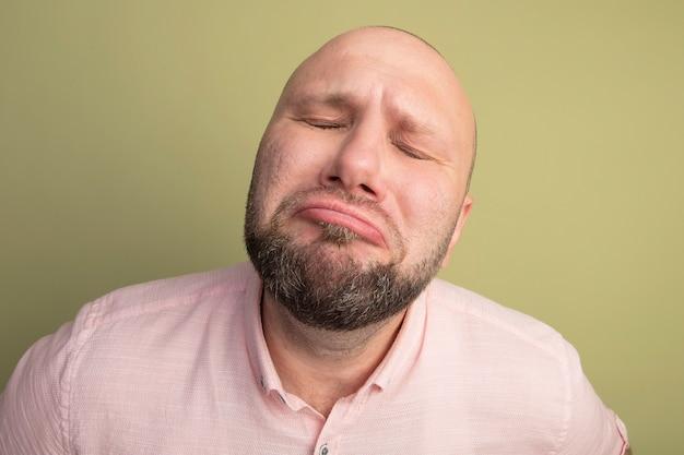 Smutny z zamkniętymi oczami łysy mężczyzna w średnim wieku ubrany w różową koszulkę