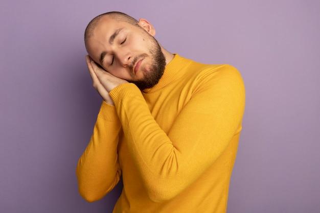 Smutny z zamkniętymi oczami młody przystojny facet pokazuje gest snu na białym tle na fioletowej ścianie