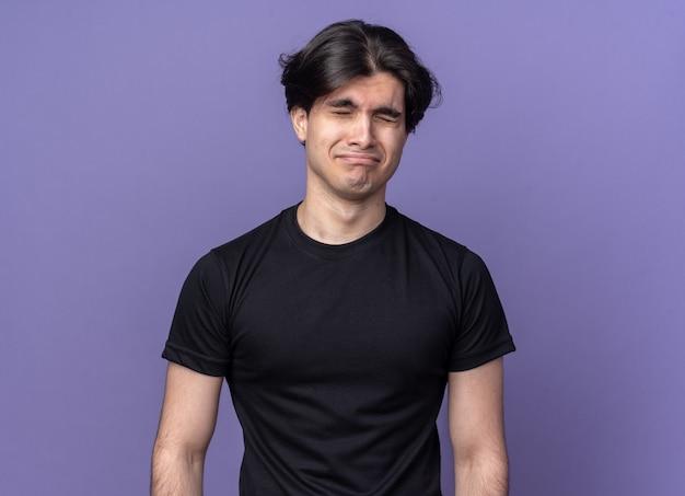 Smutny z zamkniętymi oczami młody przystojny facet ubrany w czarną koszulkę odizolowaną na fioletowej ścianie