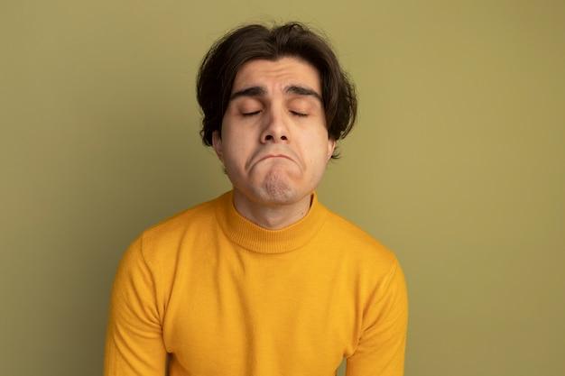 Smutny z zamkniętymi oczami młody przystojny facet ubrany w żółty sweter z golfem na białym tle na oliwkowej ścianie