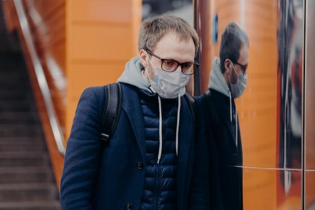 Smutny zarażony mężczyzna nosi ochronną maskę medyczną przed koronawirusem, pozuje w metrze lub metrze, chroni się przed chorobami zakaźnymi, nosi plecak. transport publiczny podczas covid-19 w europie