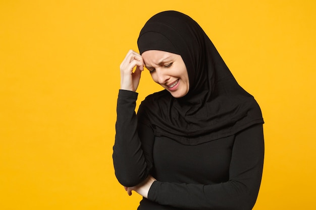 Smutny zdenerwowany płacz zdezorientowany młoda arabskiej muzułmanki w hidżab czarne ubrania pozowanie na białym tle na żółtą ścianę portret. koncepcja życia religijnego islamu ludzi.