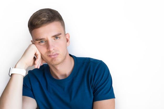 Smutny zdenerwowany sfrustrowany młody człowiek, sam nieszczęśliwy przystojny facet ma negatywne myśli, problemy, kłopoty, depresję, depresję. stres, samotny nastrój. zmęczony życiem. biała, kopia przestrzeń
