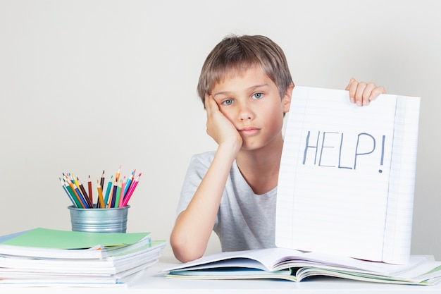 Smutny zmęczony chłopiec odrabiania lekcji i trzymając notebook z pomocą słowa