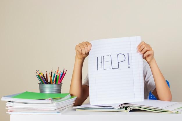 Smutny, zmęczony chłopiec potrzebuje pomocy w odrabianiu prac domowych w domu