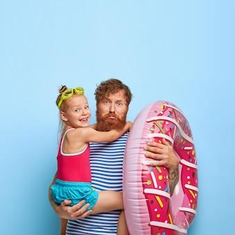 Smutny zmęczony ojciec z rudą brodą, niesie małą córeczkę na rękach, nadmuchane pływanie, wspólne chodzenie na plażę, ubrany niedbale, zabawę w odpowiednim miejscu