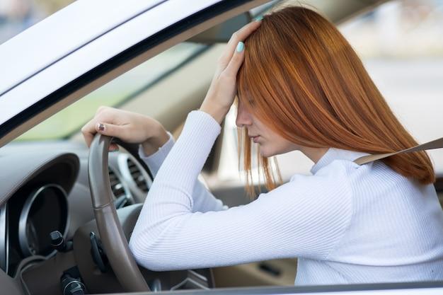 Smutny zmęczony yound kobieta kierowca siedzi za kierownicą samochodu w korku.