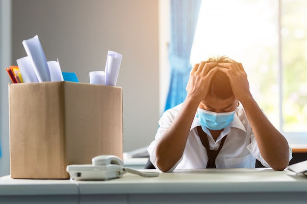 Smutny zwolniony azjatycki biznesmen siedzący poza pokojem po tym, jak został zwolniony z koncepcji porażki biznesowej i problemu bezrobocia z powodu globalnego wpływu covid-19.