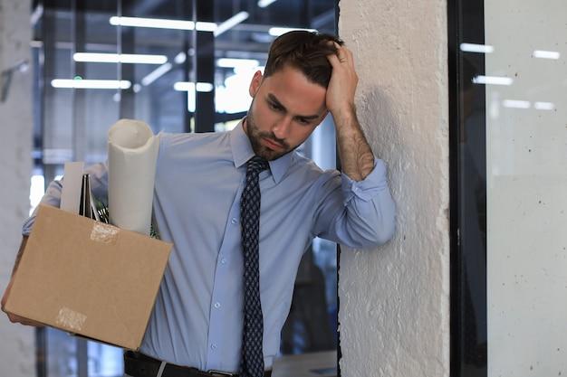 Smutny zwolniony pracownik zabiera z biura swoje przybory biurowe.