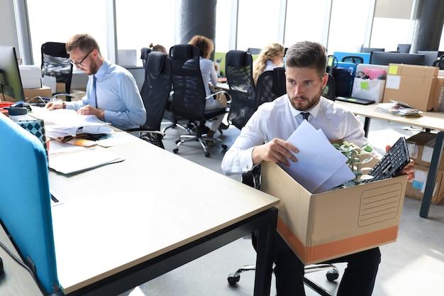 Smutny zwolniony pracownik zabiera ze sobą przybory biurowe z biura.
