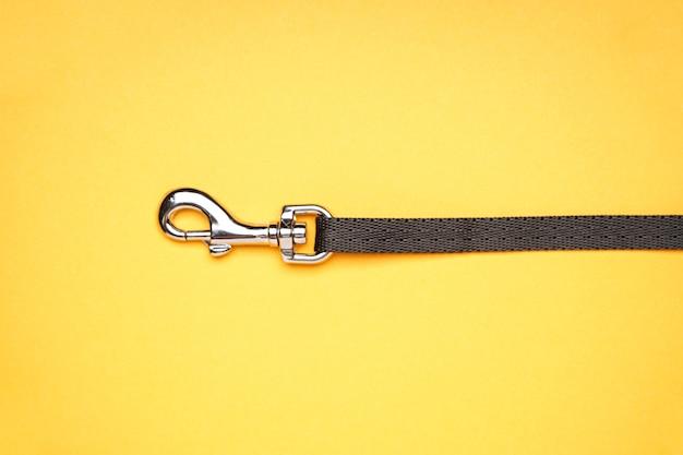 Smycz dla psa z karabińczykiem na żółtym tle, zbliżenie.