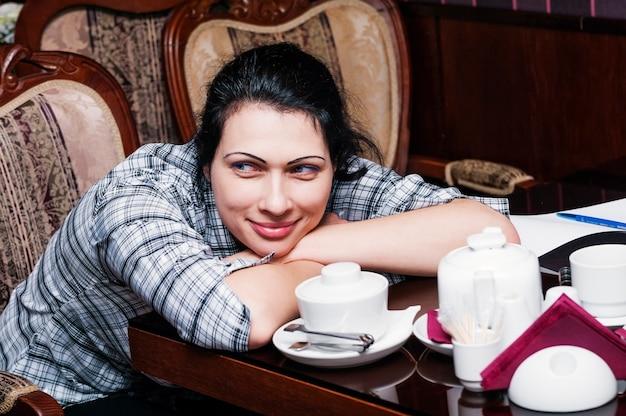 Śniąca kobieta siedzi przy stoliku w kawiarni