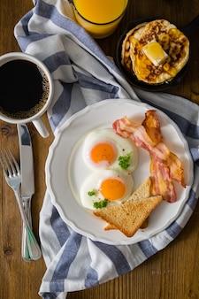 Śniadanie amerykańskie ze słonecznymi bocznymi jajkami, boczkiem, tostami, naleśnikami, kawą i sokiem