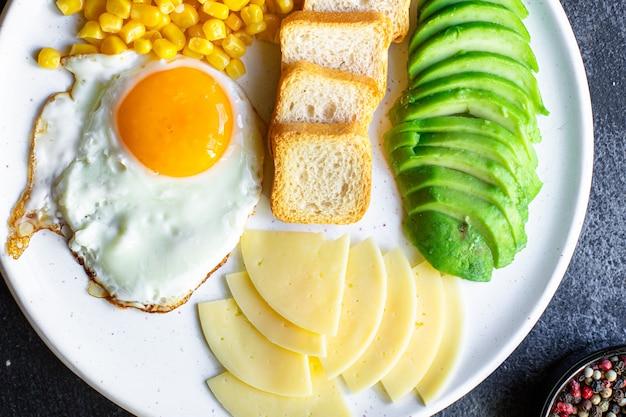 Śniadanie angielskie jajka sadzone chleb tosty warzywa ser kukurydziany i więcej gotowe do spożycia na stole