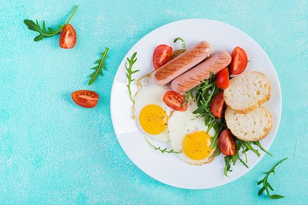 Śniadanie angielskie - jajka sadzone, kiełbaski, pomidory i świeża rukola