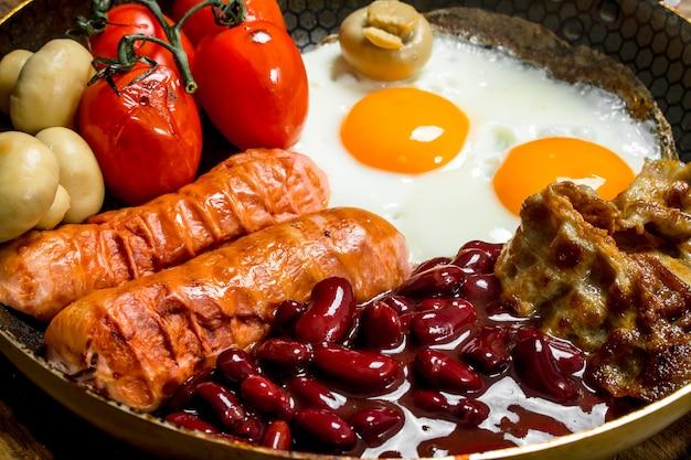 Śniadanie angielskie jajka smażone z kiełbasą, boczkiem i czerwoną fasolą w puszkach. na drewnianej powierzchni.