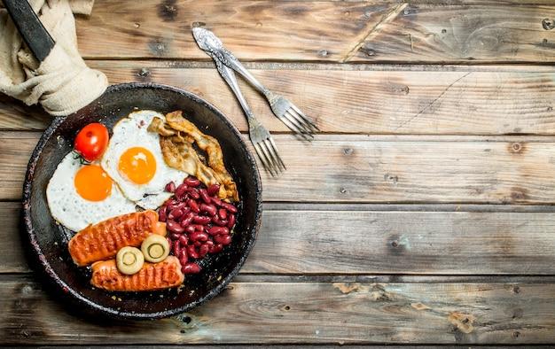 Śniadanie angielskie jajka smażone z kiełbasą, pieczarkami i fasolą. na drewnianej powierzchni.