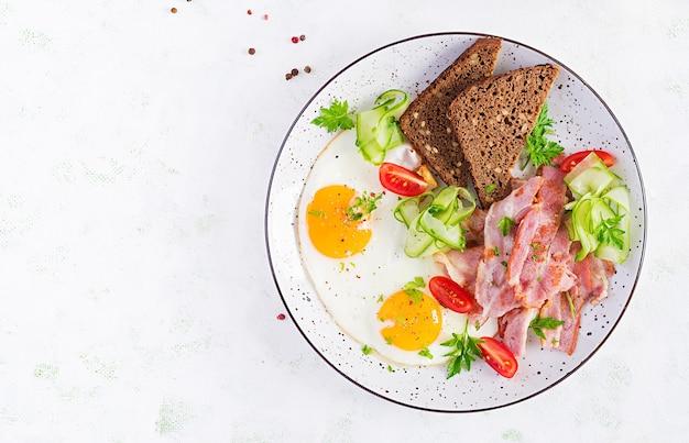Śniadanie angielskie - jajko sadzone, bekon, pomidory i pieczywo. widok z góry, płasko ułożony, nad głową