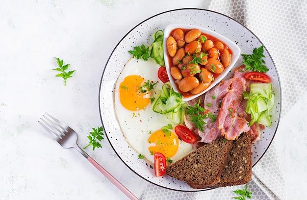 Śniadanie angielskie - jajko sadzone, fasola, bekon, pomidory i pieczywo. widok z góry, płasko ułożony, nad głową