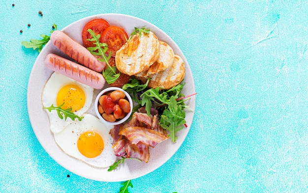 Śniadanie angielskie - jajko sadzone, fasola, pomidory, kiełbasa, bekon i grzanka