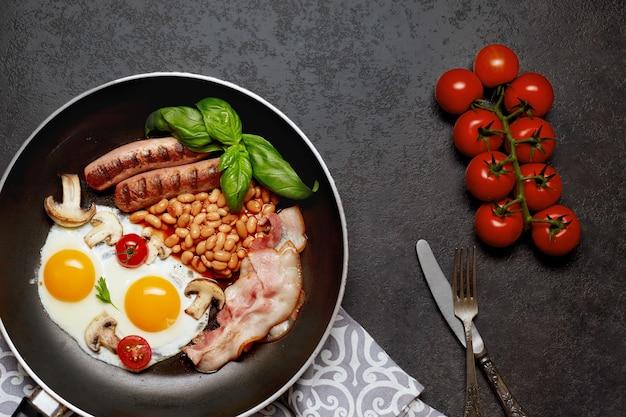Śniadanie angielskie na patelni z jajkiem sadzonym, kiełbasą, fasolą, pomidorami, pieczarkami, boczkiem i grzanką na drewnianym stole. skopiuj miejsce. widok z góry