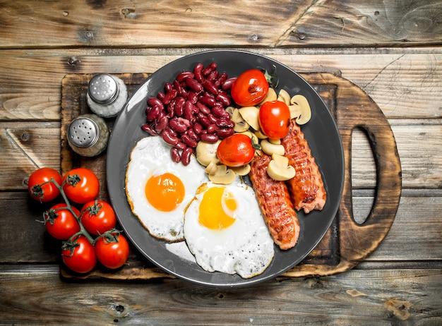 Śniadanie angielskie, smażone jajka z kiełbasą, pieczarkami i fasolą na rustykalnym stole.