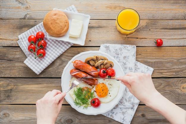 Śniadanie angielskie z jajkiem sadzonym, kiełbasą, grzybami, grillowanymi pomidorami i świeżym sokiem pomarańczowym na rustykalnym drewnianym stole. widok z góry