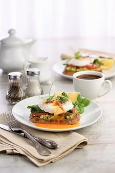 Śniadanie. best eggs benedict na kromce tostowego chleba zbożowego z guacamole i szpinakiem