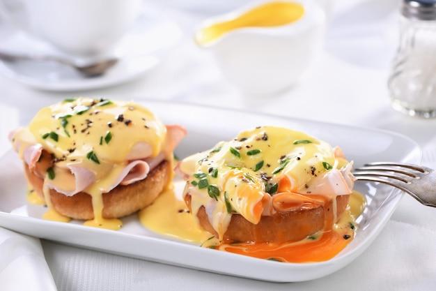 Śniadanie. best eggs benedict - smażona angielska bułka, szynka, jajka w koszulce i pyszny sos maślany holenderski