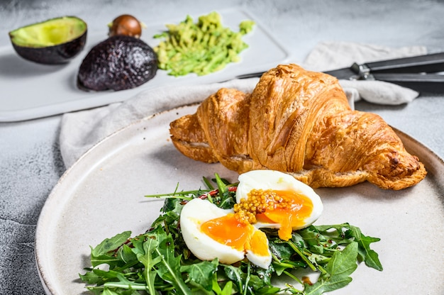 Śniadanie, brunch z avacado, rukolą, rogalikiem i jajkiem. widok z góry
