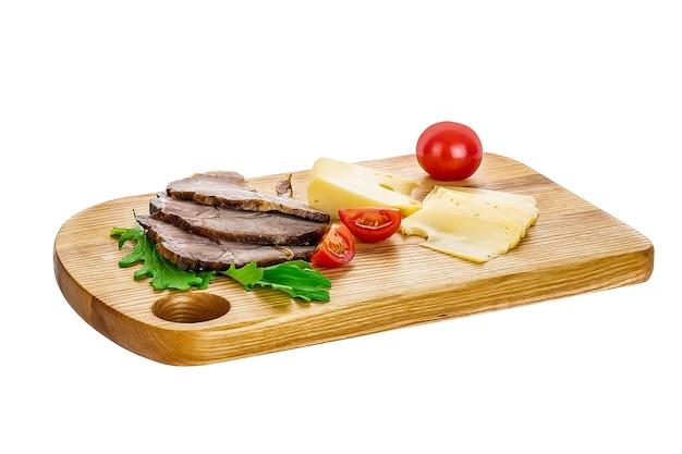 Śniadanie - chleb, szynka i ser na desce, na białym tle.