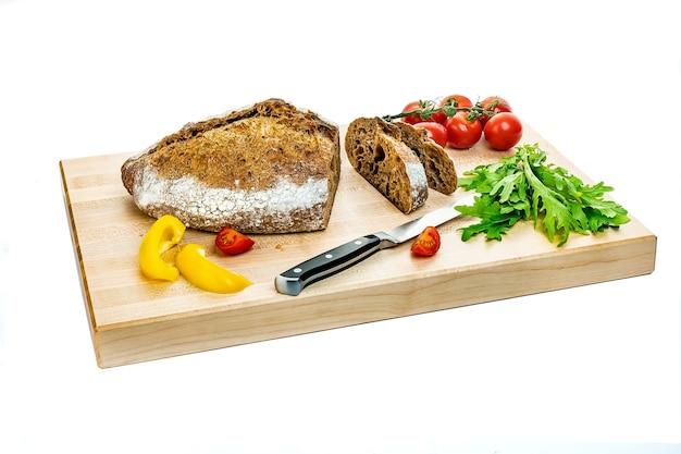 Śniadanie - chleb, szynka, pomidory i ser na desce, na białym tle